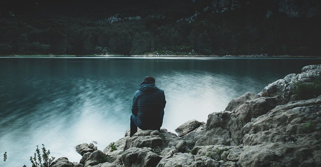 sad man sitting on rocks thinking