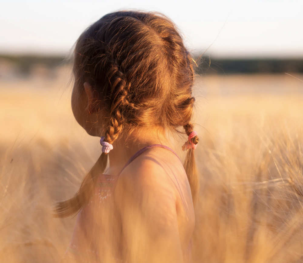 young child walking in a wheat field