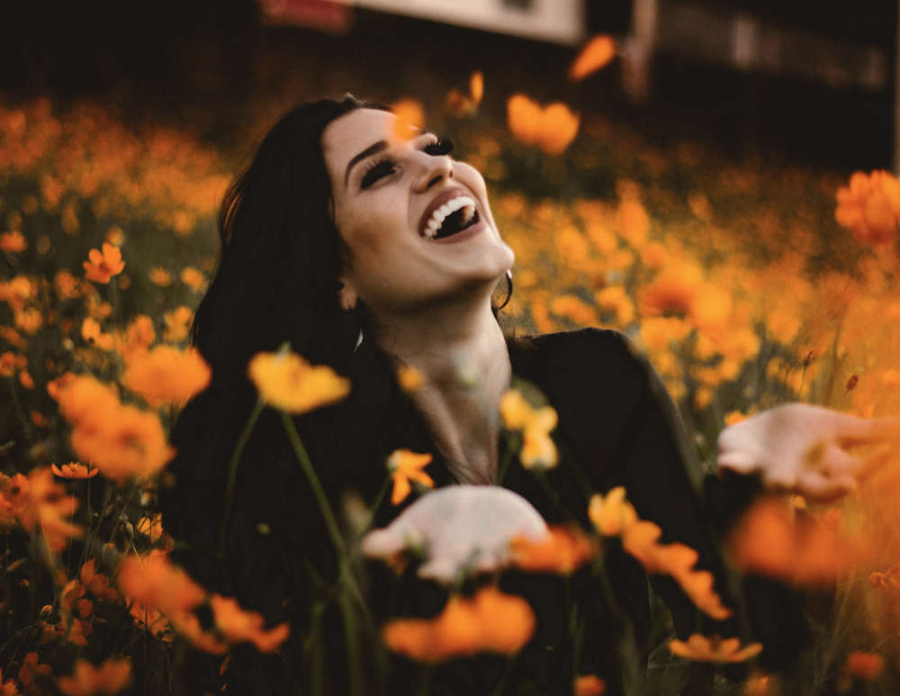 happy woman playing in a field of flowers